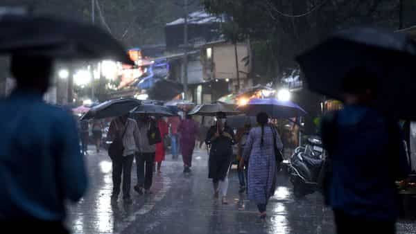 People holding an umbrella walk on the road in the rain at Andheri, in Mumbai.