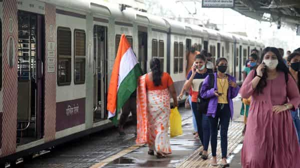 People arrive by a local train at a railway station in Mumbai.
