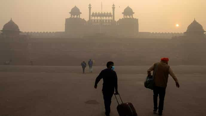 FILE PHOTO: People arrive to visit the Red Fort on a smoggy morning in the old quarters of Delhi, India. The country last revised its air pollution standards in 2009.