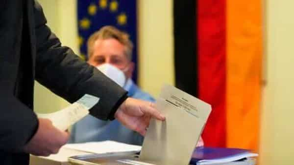 A man casts his vote for Germany's national parliament election at a polling station in Berlin, Germany, Sunday, Sept. 26, 2021. (AP)