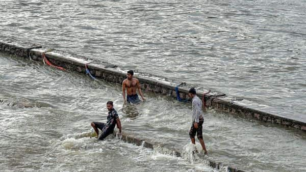 Hyderabad: People swim in the overflowing Musi river in Hyderabad, Wednesday (PTI)
