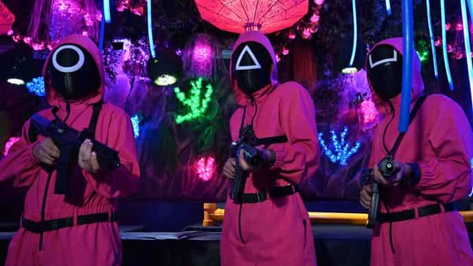 Waiters dressed in outfits from the Netflix series pose while playing a game to attract customers at a cafe in Jakarta on 19 October.