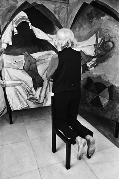 The artist kneeling before his painting of Mother Teresa, whom he held in high regard, 1993.