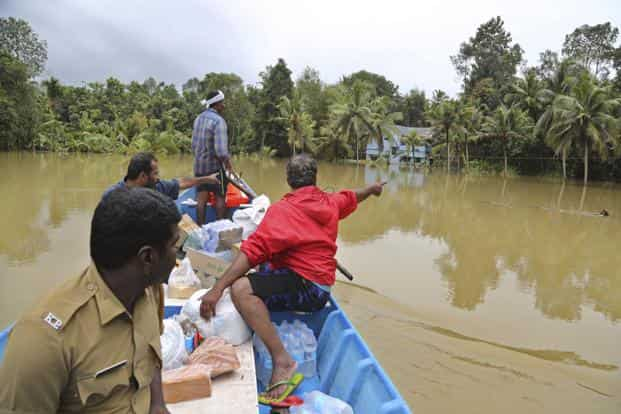 Volunteers travel in a boat with essential supplies for stranded people in a flooded area in Chengannur in Kerala. Photo: AP
