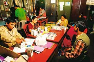Dangerous cure: Medical officers handing out monthly doses of antiretroviral medicines to two HIV+ patients (back to the camera) at the Calcutta Rescue Clinic, Tala Park, in Kolkata. Indranil Bhoumik/