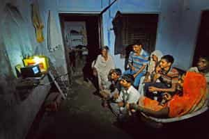 Ray of hope: The Sharma household in front of an 8-inch television set. They work the black-and-white TV set with the help of a solar panel that the family has purchased for Rs2,500 from Ghaziabad. Pr