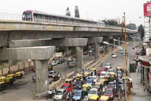 A Metro train moves along an elevated track past waiting traffic on the street below in Bangalore. Photo: Bloomberg