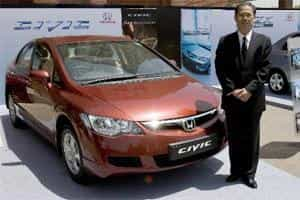 File photo of Masahiro Takedagawa, president and chief executive officer of Honda Siel Cars India Ltd., poses for a picture next to a Honda Civic in Jaipur. Bloomberg