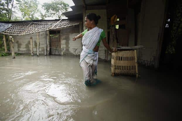 A woman stands outside her flooded home in a village near Guwahati. AP