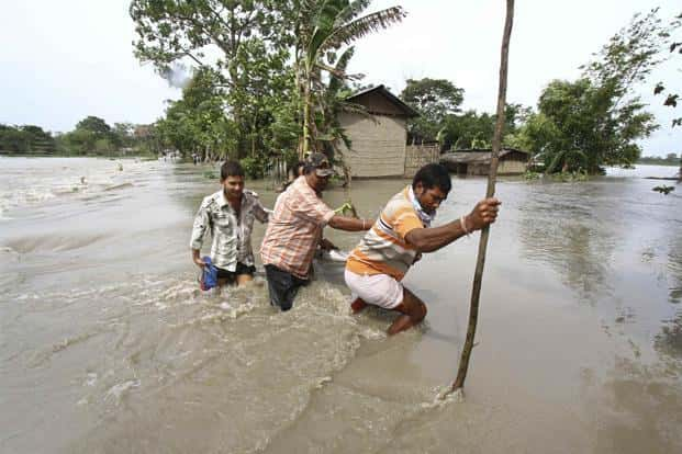 Villagers cross a flooded road at Lachi Bishnupur village. Reuters
