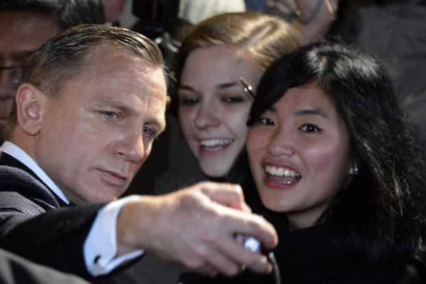Daniel Craig (left) in his third Bond movie poses for a photograph with fans as he arrives for the world premiere of