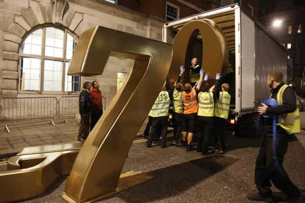 Workers load a metal 007 sign into a truck taking it to storage, after