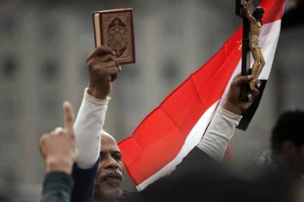 An Egyptian protester holds up a Koran and a figure of Christ on the cross during a demonstration against Mursi. AFP