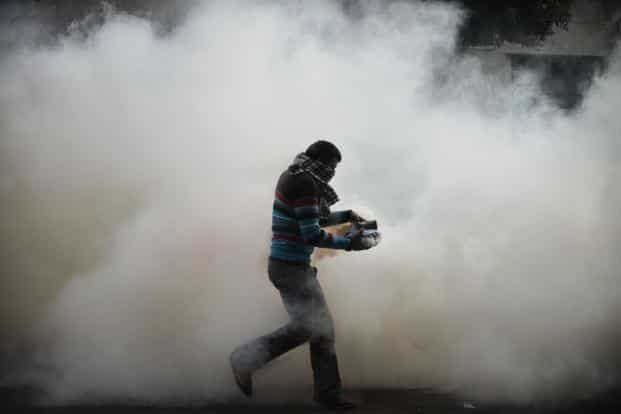An Egyptian protester attempts to throw a tear gas canister during clashes with the Egyptian Riot Police in Omar Makram Street, Tahrir Square. AFP