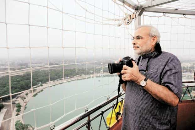Narendra Modi takes photographs as he rides in a tethered helium balloon, the 'Ahmedabad Eye'. Photo: AFP