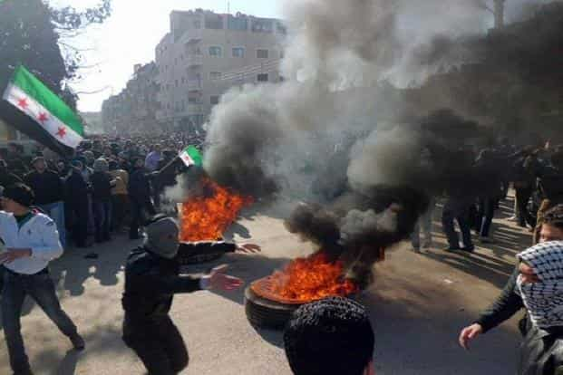 Protesters burn tires and waving independence flags during an anti-regime demonstration in the Daraya, Damascus on 4 February 2012.