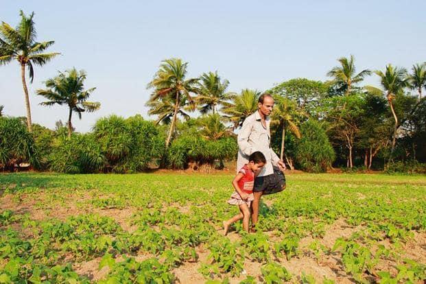 Village priest Samantray takes a walk in his homestead with granddaughter Haripriya. Photo: Chitrangada Choudhury