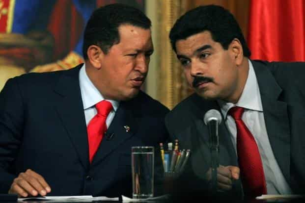 In this file photo taken on 17 October 2006, Venezuelan President Hugo Chavez speaks with the then Venezuelan foreign minister Nicolas Maduro in Caracas. Maduro was handpicked by former Venezuelan President Hugo Chavez to be his successor AFP