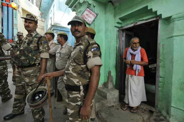 Police stand outside a Hindu temple in Ayodhya. Sunday saw a game of hide-and-seek being played out with VHP leaders trying to sneak in to various hideouts to start their yatra while police kept vigil on every street to prevent them from doing so. AP