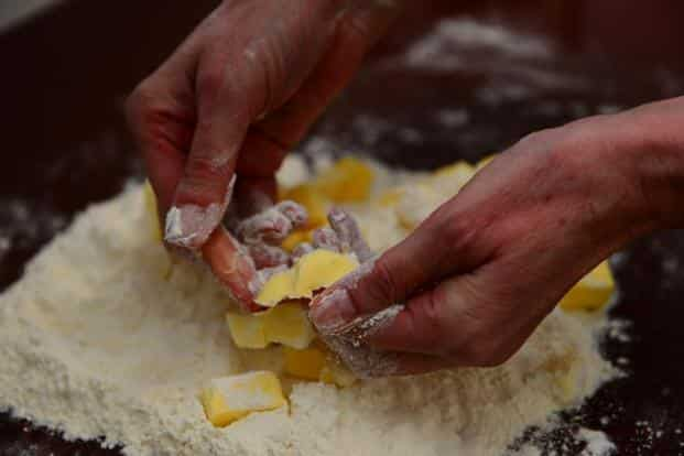 Squeeze the butter cubes between your thumb and fingers into the flour.