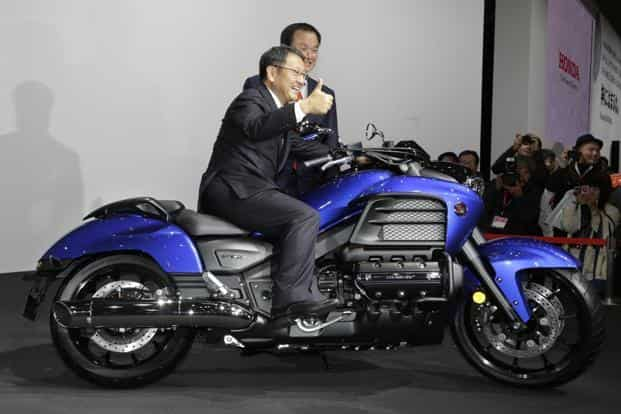 Toyota Motor Corp. president Akio Toyoda gives the thumbs-up as he rides on a Honda Gold Wing F6C motorcycle.  The Gold Wing F6C has a new aluminium subframe, new styling and steering geometry and radiators mounted on the sides instead of the front. AP