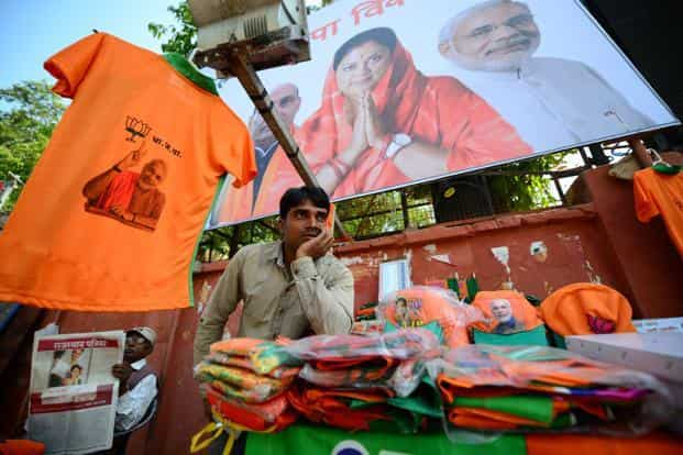 A vendor sells t-shirts and caps with the Bharatiya Janata Party (BJP) logo in Jaipur before the assembly elections. CM Ashok Gehlot is in tough competition with former chief minister and BJP's chief ministerial candidate Vasundhara Raje in the state. Pradeep Gaur/Mint