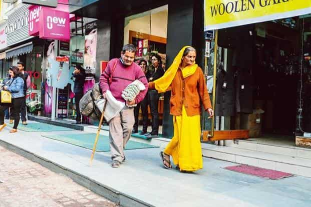 Laxmikant Shukla sells mops and dusters in Khan Market and is accompanied by his wife Indu.