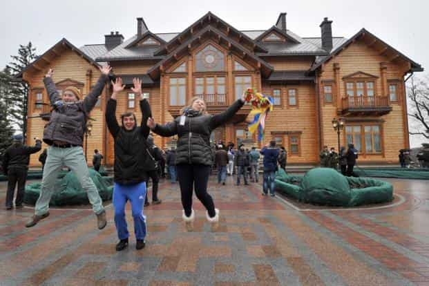 People express their joy in front of the main building of Ukrainian President Viktor Yanukovych's residency. AFP