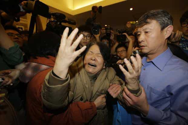 A family member of a passenger aboard Malaysia Airlines MH370 cries after watching a television broadcast at the Lido hotel in Beijing of the Malaysian prime minister announcing that the jet ended its journey in the remote Southern Indian Ocean on 24 March. Reuters