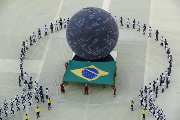 A view of the ceremony as artists carry Brazil's national flag. Photo: AFP