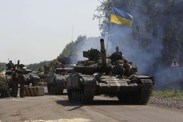 Ukrainian army tanks move past a checkpoint as they patrol the area near eastern Ukrainian town of Debaltseve on Sunday. Photo: Reuters