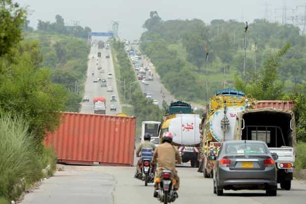 Empty containers to be used as roadblocks lie on a highway ahead of a march by the opposition in Islamabad. Photo: AFP