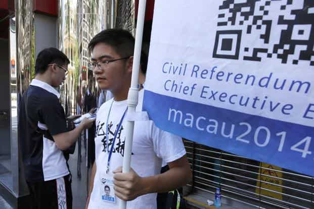 A man (left) votes on a tablet, behind a volunteer with a banner in support of an informal civil referendum in Macau. Photo: AP