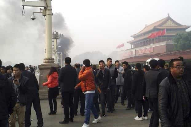 People walk along the sidewalk of Chang'an Avenue as smoke rises in front of the main entrance of the Forbidden City at Tiananmen Square in Beijing in this file photo from October 2013. Photo: Reuters
