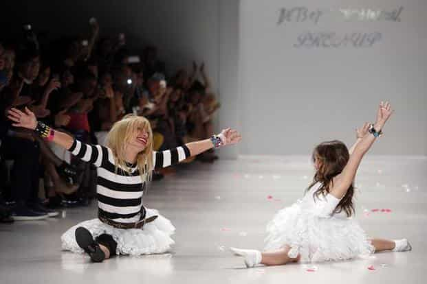 Designer Betsey Johnson, left, does a split after cartwheeling with her granddaughter, Layla Margulies, during the finale of her Spring 2015 fashion show during FashionWeek in NewYork. AP