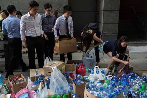 Office workers organize water supplies for the protesters near the central government offices in the business district in Hong Kong. Bloomberg
