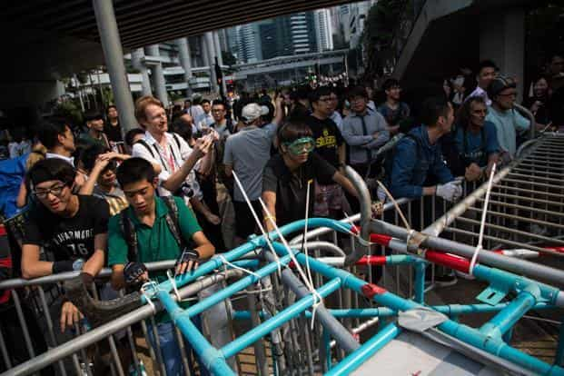 Pro-democracy protesters stand behind a barricade during clashes with anti-Occupy demonstrators, unseen, on Queensway in Hong Kong. Photo: Bloomberg