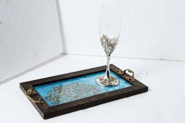 Wooden tray with 'nakkashi', `2,050, and wine glass (set of two), `3,150, Ishatvam, Sultanpur, MG Road, New Delhi, www.facebook.com/Ishatvam