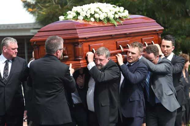 The coffin of Australian batsman Phillip Hughes is carried by family members and fellow cricketers from the hall. Photo: AFP