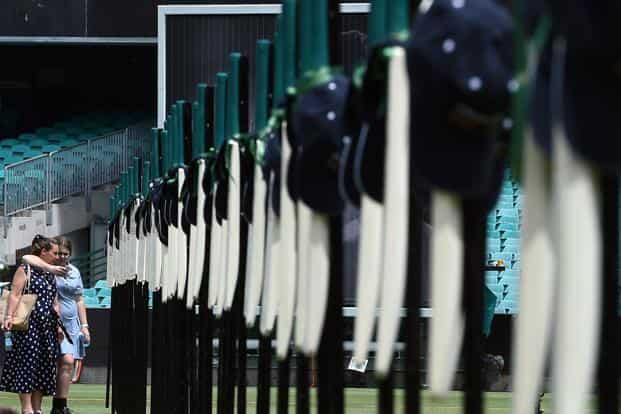 Mourners look at the 63 bats detailing the career of cricketer Phillip Hughes during a memorial service at the Sydney Cricket Ground. Photo: AFP