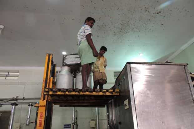 Two workers aloft an electric lift, overseeing the mixing process.