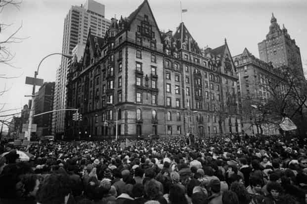 Crowds gathered outside the home of John Lennon in December 1980 in New York after the news that he had been shot and killed. A flag flies at half-mast over the building. Getty Images