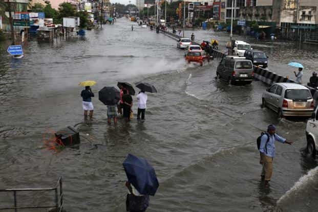 People stand on a street that was flooded following heavy rains in Chennai, Tamil Nadu on 16 November. Photo: AP