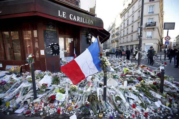 A French flag flies over flowers, candles and messages in tribute to victims outside 'Le Carillon' restaurant a week after a series of deadly attacks in Paris, France. Photo: Reuters