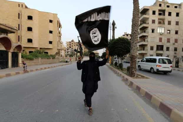 A file photo of a member loyal to the Islamic State waving an IS flag in Raqqa on 29 June 2014. Photo: Reuters