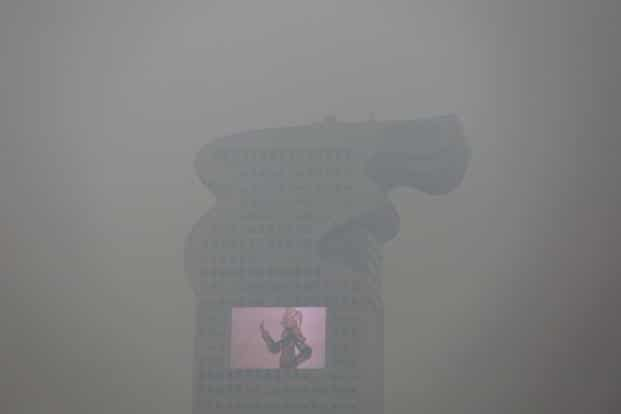 The visibility in the city also falls by early evening because of the thick layer of smog. Here, a building in Beijijng and a bright screen on it is barely visible through the smog. Reuters