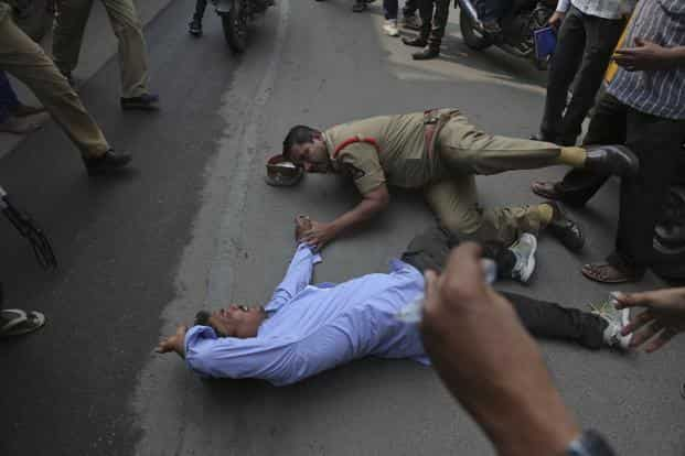 A police officer slips while trying to restrain a man who was participating in a protest over the suicide of Rohith Vemula, in Hyderabad on 25 January 2016. Photo: AP