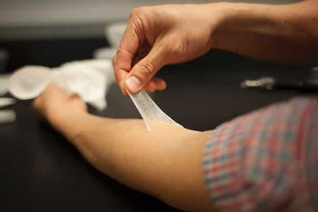 A person peeling off a 'Second skin' a new material that temporarily tightens skin, a polymer that could also be used to protect dry skin and deliver drugs. Photo: AFP/MIT/Melanie Gonick