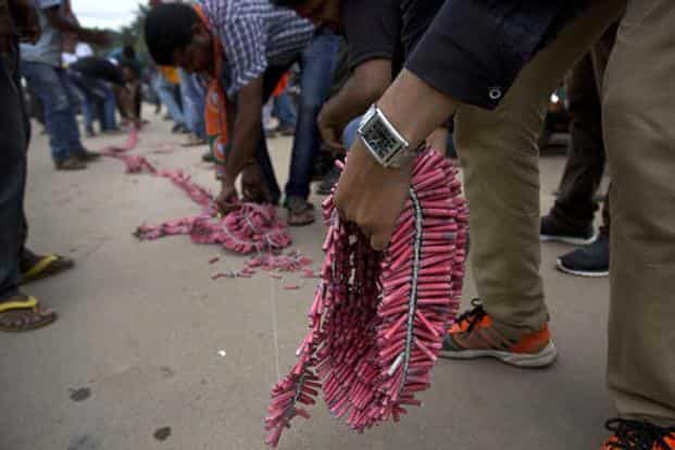 BJP supporters light firecrackers to celebrate the party's victory in the Assam assembly election on Thursday. Photo: PTI