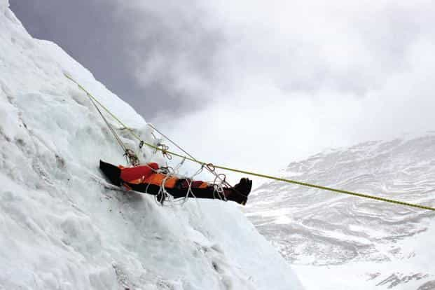 A corpse of a mountaineer being retrieved by unseen Nepalese sherpas at Mount Everest. Photo: Namgyal Sherpa/AFP